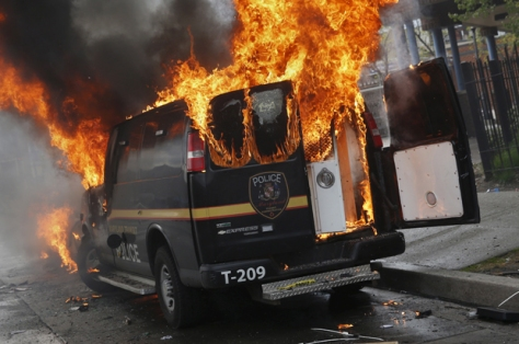 A Baltimore Metropolitan Police transport vehicle burns during clashes in Baltimore